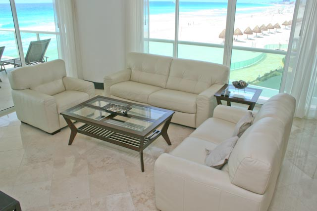 Another view of the extra large great room with contemporary furniture, ocean view and open to modern kitchen